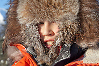 Young boy stays warm in winter with a fur hat.
