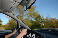 Woman's hands on steering wheel inside a speeding car on highway, Provence, France (blurred motion)