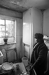 Woman alone in damp kitchen of her Hoxton high rise flat London 1978.