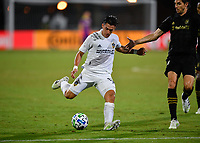 LAKE BUENA VISTA, FL - JULY 18: Cristian Pavón #10 of LA Galaxy shoots the ball while pressured by Dejan Jakovic #5 of LAFC during a game between Los Angeles Galaxy and Los Angeles FC at ESPN Wide World of Sports on July 18, 2020 in Lake Buena Vista, Florida.
