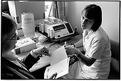 A nurse talsk to a patient before a computerised blood cholesterol level test at St.Mary's Hospital pathology department, London.