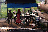 A warung (coffee shop) set up beside massive pipes used to pump mud into the Porong River, at Besuki Village. Since May 2006, more than 10,000 people in the Porong subdistrict of Sidoarjo have been displaced by hot mud flowing from a natural gas well that was being drilled by the oil company Lapindo Brantas. The torrent of mud - up to 125,000 cubic metres per day - continued to flow three years later.