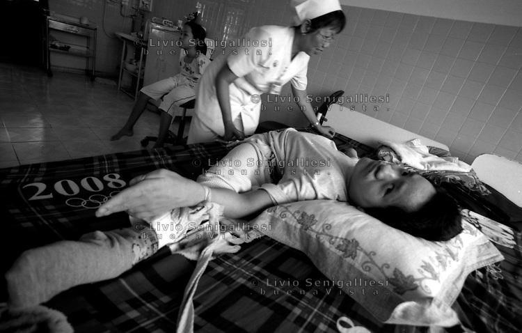 Tu Du Hospital - Ho Chi Minh City / Vietnam.<br /> Conseguenze guerra in Vietnam 40 anni dopo.Nguyen Viet, 24 anni, vittima dell'agente arancio proviene dal villaggio di Sa Thay, una delle zone più contaminate dalla diossina. Vegeta letteralmente nel letto nel reparto lungo-degenti del Tu Du Hospital, mentre il fratello gemello Duc meno segnato dalla sidrome, grazie alle cure conduce una vita quasi normale.<br /> Foto Livio Senigalliesi.<br /> Tu Du Hospital - Ho Chi Minh City / Vietnam.<br /> Hospital for victims of Agent Orange / Dioxine Syndrome.In the picture Nguyen Viet (24) born in the village Sa Thay, one of the places most contaminated by the deadly herbicide.Viet has been vegetating in his bed, attended by the nurses and by his mother La Thi (52) sprayed during the war times by US airplanes.<br /> Photo Livio Senigalliesi