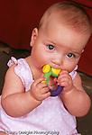 8 month old baby girl sitting, closeup, biting teething ring