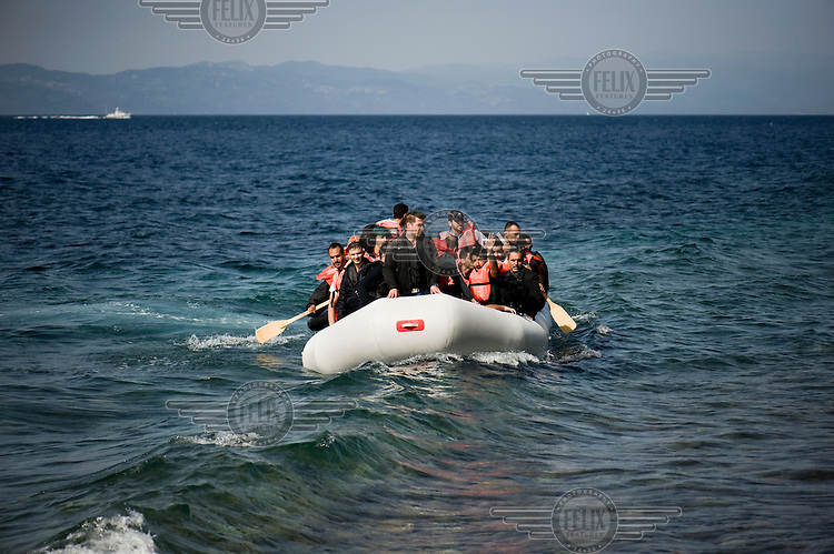 A group of Syrian refugees on a small inflatable boat near the beach of Skala Sykaminias on the island of Lesbos. On the horizon the Greek Coast Guard vessel can be seen. Every day hundreds of refugees, mainly from Syria and Afghanistan, are crossing in small overcrowded inflatable boats the six mile channel from the Turkish coast to the island of Lesbos in Greece. Many spend their life savings, over $1,000, to buy a space on these boats.