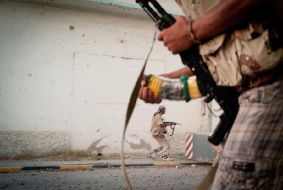 Rebel fighters engage Gaddafi troops in the Bab Al Aziziya compound in Tripoli, Libya