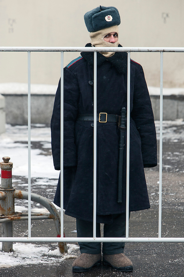 Moscow, Russia, 13/01/2013..A policeman watches as thousands of opposition protesters carry posters of President Vladimir Putin and members of the Russian parliament with the word ?Shame? written in red at a protest called the March Against The Scoundrels. The protest was against the new law banning the adoption of Russian children by Americans, widely seen as a response to the recently passed USA Magnitsky Act.