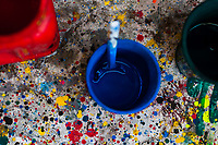 "Plastic cups filled with paint are seen placed on a splattered kerb in the sign painting workshop in Cartagena, Colombia, 13 April 2018. Hidden in the dark, narrow alleys of Bazurto market, a group of dozen young men gathered around José Corredor (""Runner""), the master painter, produce every day hundreds of hand-painted posters. Although the vast majority of the production is designed for a cheap visual promotion of popular Champeta music parties, held every weekend around the city, Runner and his apprentices also create other graphic design artworks, based on brush lettering technique. Using simple brushes and bright paints, the artisanal workshop keeps the traditional sign painting art alive."