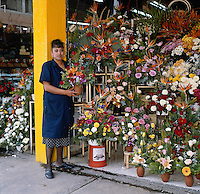 Flower vendors of Mexico City, series - young woman holding flower arrangement in front of flower stall. Mexico City Distrito Federal Mexico.