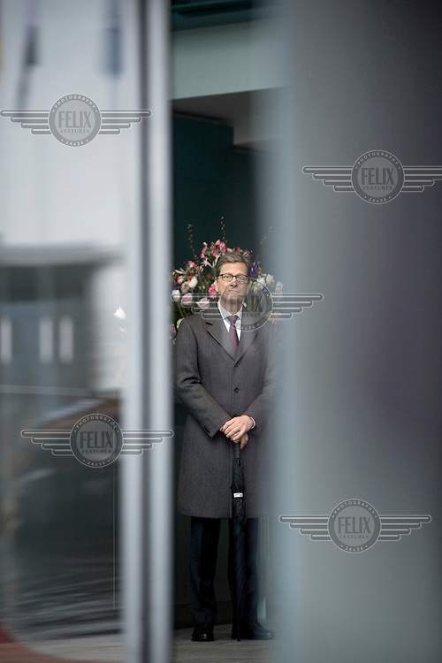 DEU, Deutschland, Germany, Berlin, 30.01.2013.Guido Westerwelle, Federal Minister of Foreign Affairs, FDP, is waiting for the egypt premier minister at the entrance of the Chancellery in Berlin, Germany. International Politics, German, Germany, Europe, Politican, Portrait, 2013.