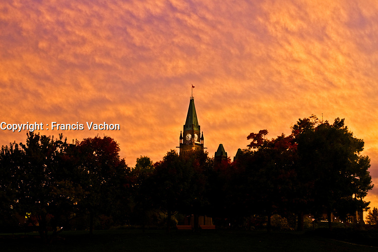 Sun set on the Parliament Peace Tower in Ottawa Monday September 27, 2010. Parliament Hill (colloquially The Hill, in French: Colline du Parlement) is an area of Crown land on the southern banks of the Ottawa River in downtown with a Gothic revival suite of buildings, the parliament buildings, that serves as the home of the Parliament of Canada and contains a number of architectural elements of national symbolic importance.<br /> <br /> PHOTO :  Francis Vachon - Agence Quebec Presse