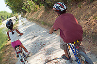 Young boy and girl biking side by side, Carcassonne, Canal du Midi, France.