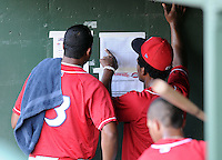 Members of the Lakewood BlueClaws look over the lineups posted to the dugout wall prior to a game against the Greenville Drive on July 12, 2011, at Fluor Field at the West End in Greenville, South Carolina. (Tom Priddy/Four Seam Images)