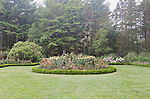 Rose Garden in large lawn, in Shore Acres State Park botanical gardens, an Oregon State Park that adorns Cape Arago on the Pacific Ocean coast of Oregon.  Cape Arago on the Central Oregon Coast with views of Sunset State Park and the Umpqua River Lighthouse, and massive headlands. Near Coos Bay, Oregon, Cape Arago is known for its rugged views, hiking, wildlife, beach access, and Sunset Beach State Park and unique geology.