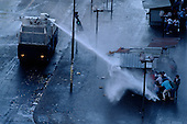 """Santiago, Chile<br /> October 1988<br /> <br /> Police disperse demonstrators who demand the immediate removal of General Pinochet with powerful water cannons.<br /> <br /> In October 1988, General Augusto Pinochet ordered a plebiscite vote asking Chilean citizens whether he should continue in office. It produced a decisive """"no"""" vote and the following year he lost the first presidential election in 19 years. However, under a constitution crafted by his advisors, he remained as army commander until 1998. Pinochet continued to wield enormous power until his arrest in London on human rights charges in October 1998."""