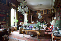 Two grand chandeliers hang from ceiling roses in the library. Today it is used as the families main sitting room. It is also one of the rooms refreshed by Tom Parr and Vivien Greenoch of Colefax and Fowler
