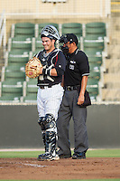 Kannapolis Intimidators catcher Brett Austin (10) and home plate umpire Takahito Matsuda during the game against the Delmarva Shorebirds at CMC-NorthEast Stadium on July 2, 2014 in Kannapolis, North Carolina.  The Intimidators defeated the Shorebirds 6-4. (Brian Westerholt/Four Seam Images)