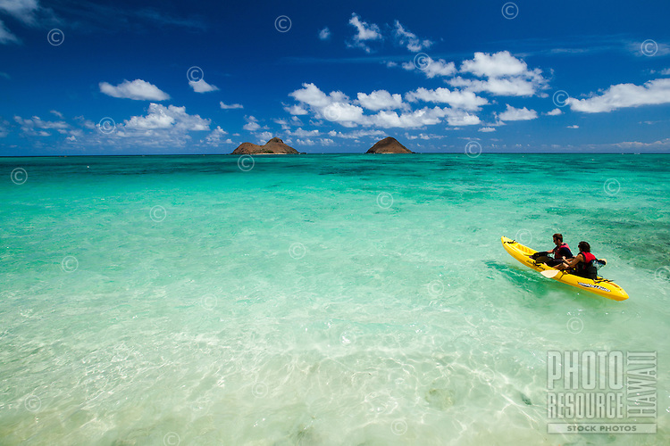 A couple in a kayak start their journey to the Mokulua Islands on a crystal clear day at Lanikai Beach, O'ahu; translucent water reveals the reef and white sand.