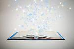 Shiny stars flying over open book