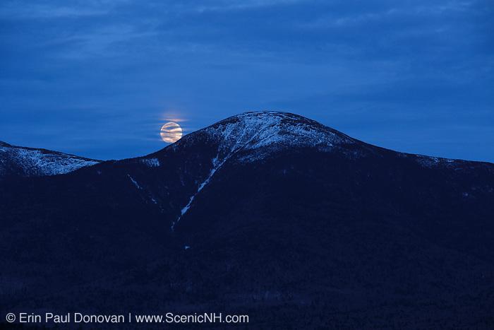 Moonrise behind Mount Eisenhower in the White Mountains of New Hampshire during the spring months. Mount Eisenhower is part of the Presidential Range.