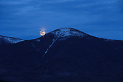 Moonrise behind Mount Eisenhower in the  White Mountains of New Hampshire USA during the spring months. Mount Eisenhower is part of the Presidential Range.