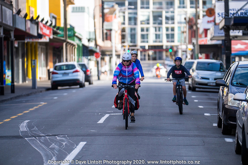A family cycles down Cuba Street at 3pm on Thursday during lockdown for COVID19 pandemic in Wellington, New Zealand on Thursday, 9 April 2020. Photo: Dave Lintott / lintottphoto.co.nz