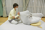 A therapist wraps a man in cloth during an Otonamaki (adult wrapping) therapy session on February 4, 2017, Tokyo, Japan. Otonamaki is a Japanese therapeutic method to reduce stiffness and posture problems. A participant, monitored by a health care professional is wrapped in a large piece of breathable cloth, like a sheet, to alleviate posture problems and body stiffness for about 15 to 20 minutes. The therapy comes from Ohinamaki, the practice of wrapping up babies in cloth in a similar way to give them a feeling of security and help them with their physical development. (Photo by Rodrigo Reyes Marin/AFLO)