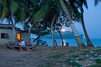 Tamil man sits outside his home at dawn with Barberyn (Beruwala) light in background - Beruwala, Sri Lanka
