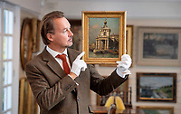 BNPS.co.uk (01202 558833)<br /> Pic: ZacharyCulpin/ BNPS<br /> <br /> Pictured: Auctioneer, Clifford Lansberry of Gorringe's holding the painting.<br /> <br /> A 'lost' painting by the Italian master Canaletto that was found hanging in the drawing room of an English home after 100 years sold for over £380,000.<br /> <br /> The 18ins by 12ins oil on canvas work was bought in London in 1920 for about £100 - £5,000 in today's money - by the mother of the late owner who died recently.<br /> <br /> She inherited it over 50 years ago and hung it on the wall of the detached house in Lewes, East Sussex, that she moved into in 1970.