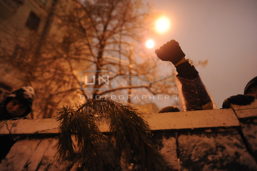Protester behind barricade.  Tonight the  police is expected to forcedly evacuate the streets from the protesters blocking all the government buildings. Kiev. Ukraine.
