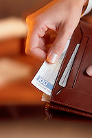 A hand taking French franks out of a wallet.