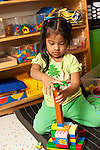 Education Preschool 4 year olds girl quietly building with colorful plastic Duplo bricks