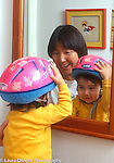 18 month old toddler boy wearing bike helmet looks at reflection of himself in mirror, with mother