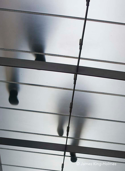 View from underneath a frosted glass walkway of pedestrians walking above.