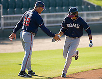 Rome Braves manager Randy Ingle #12 slaps hands with Ramon Flores #25 as he round third base following his 2-run home run against the Kannapolis Intimidators at Fieldcrest Cannon Stadium April 11, 2010, in Kannapolis, North Carolina.  Photo by Brian Westerholt / Four Seam Images