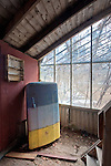 A Colorful Refrigerator in a Deserted Greenhouse