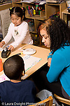 Education Preschool 3-4 year olds female student teacher working with boy talking to him girl in background works on art project vertical