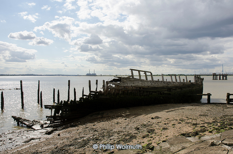 Decaying wooden hull of a ship at a disused dock on the Kent shore of the Thames estuary.