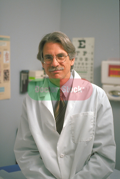 portrait of male doctor wearing lab coat in examination room