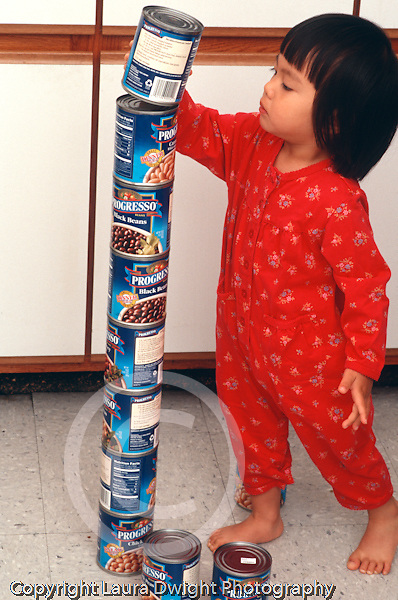 22 month old toddler girl in kitchen building tower from bean cans vertical Asian Vietnamese