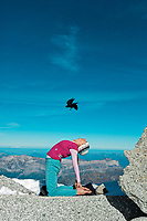 Martina Cufar practising yoga high in the Alps with MOnth Blanc in the background an Alpine Choughs (Pyrrhocorax graculus) flying above her head.