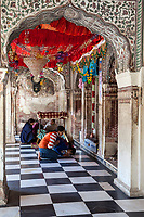 India, Dehradun.  Two Young Indian Women in Western Clothes Worship at  A Sikh Temple built in 1707--the Durbar Shri Guru Ram Rai Ji Maharaj.  In the background a woman reads sacred scripture to two women.