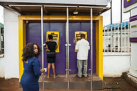 Nigeria. Enugu State. Enugu. Town center. Igbo people. A  man and a woman withdraw money at a cash machine from First City Monument Bank (FCMB) Ltd which is a full service banking group, headquartered in Lagos, with the vision 'to be the premier financial services group of African origin'. Enugu is the capital of Enugu State, located in southeastern Nigeria. 10.07.06.19 © 2019 Didier Ruef