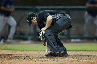 Home plate umpire Austin Jones cleans off home plate during the game between the Mississippi Braves and the Birmingham Barons at Regions Field on August 3, 2021, in Birmingham, Alabama. (Brian Westerholt/Four Seam Images)