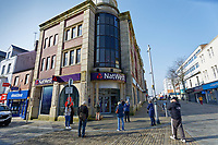 Pictured: A queue of customers observing social distancing rules outside NatWest Bank in Oxford Street, Swansea, Wales, UK. Tuesday 24 March 2020<br /> Re: Covid-19 Coronavirus pandemic, UK.