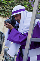 Antigua, Guatemala. Even a cucurucho wants to photograph an alfombra (carpet) of flowers, pine needles, and other traditional materials decorating the street in advance of the passage of a procession during Holy Week, La Semana Santa, the better to remember it.