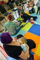 """Breastfeeding a newly arrived baby and an older toddler in tandem at a singing and signing group whilst talking to the other mothers.Image from the breastfeeding collection of the """"We Do It In Public"""" documentary photography picture library project: <br />  www.breastfeedinginpublic.co.uk<br /> <br /> <br /> Berkshire, England, UK<br /> 27/09/2013<br /> <br /> © Paul Carter / wdiip.co.uk"""