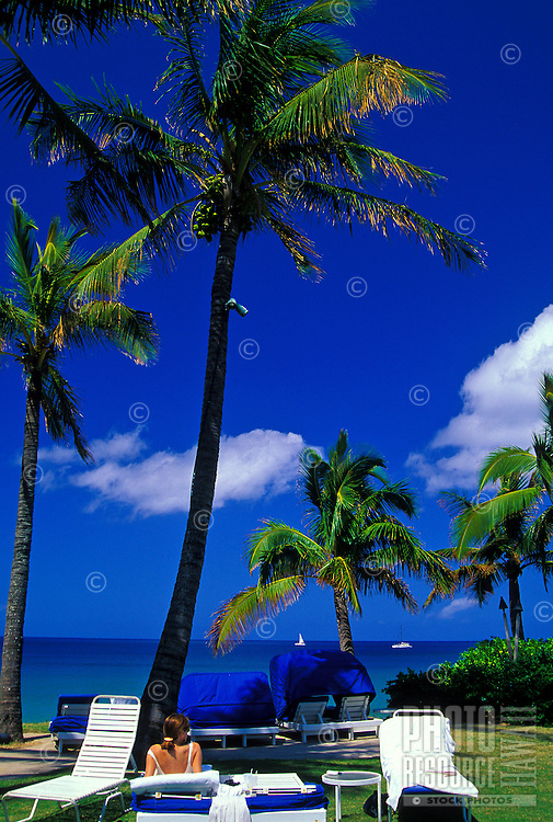At the Ritz Carlton in Kapalua, Maui, a woman relaxes and enjoys the sun under tall coconut palms.