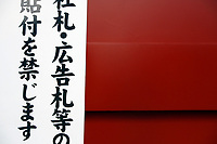 Traditional Japanese writing next to a deep red coloured wall at Sensoji, an ancient Buddhist temple, in Tokyo.