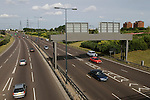 The cars on the left of this image are on the A102 (M) East Cross Route formally known as the A106 Eastway Ruckholt. They are heading north east towards towards Leyton and Wanstead. Templars tower block on right East London the site of the 2012 Olympic Games Hackney Marsh, England 2006.